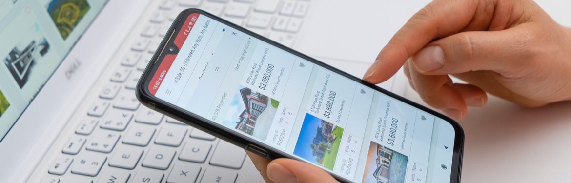 Close up of someone holding a phone looking at properties